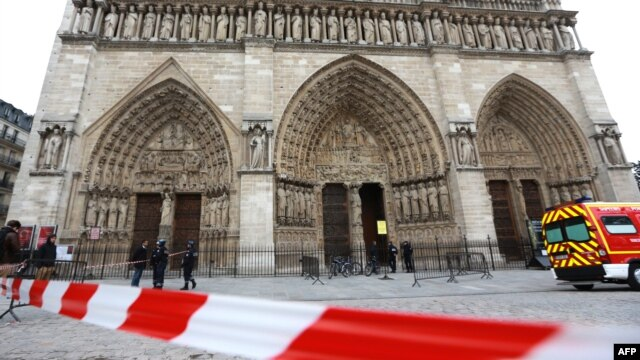 French policemen cordon off in front of Paris' Notre Dame Cathedral following the evacuation of the after a man shot himself dead in front of the altar, May 22, 2013.