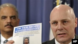 FBI Executive Assistant Director Shawn Henry (r) holds up a wanted poster during a news conference in Washington with Attorney General Eric Holder, March 9, 2011