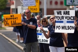 Supporters of officer Darren Wilson hold posters outside Barney's Sports Pub in St. Louis, Missouri, Aug. 23, 2014.