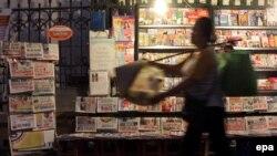 Một phụ nữ đi ngang qua sạp bán báo trên đường phố ở Hà Nội, ngày 13 tháng 4 năm 2015.