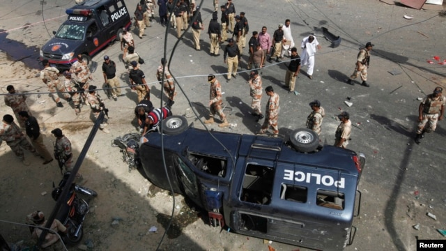 Paramilitary soldiers and police officers gather at the site of a bomb blast in Karachi, June 26, 2013.