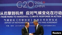 Le président américain Barack Obama, à droite, se serre la main avec le secrétaire général de l'ONU Ban Ki-moon lors d'une cérémonie de ratification conjointe de l'accord sur le changement climatique de Paris avant le sommet du G20 au Guest House de l'Etat, le 3 septembre 2016.