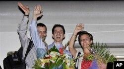 Shane Bauer (à g.), Josh Fattal (au c.) et Sarah Shourd (fiancée de Bauer) saluent le public en prenant l'avion à Mascate, Oman (24 septembre 2011)