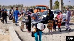 A handout picture made available by the Iranian Red Crescent on Aug. 19, 2021, shows Afghan refugees arriving at the Iran-Afghanistan border between Afghanistan and the southeastern Iranian Sistan and Baluchestan province.