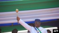 Le président de la Sierra Leone, Maada Bio, soulève le sceptre du pouvoir lors de son investiture à Freetown le 12 mai 2018.