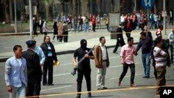 Petugas keamanan berjaga-jaga setelah serangkaian ledakan terjadi di luar kampus utama Cairo University (2/4).