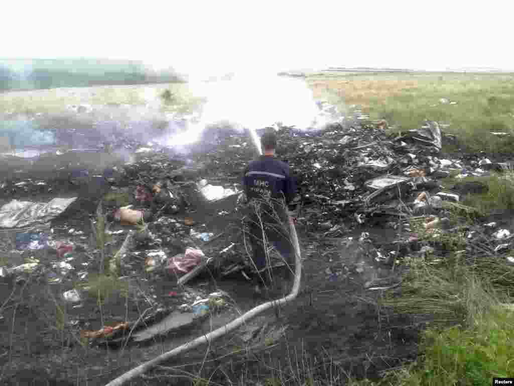 Um bombeiro tenta apagar as chamas do avião que caiu na Ucrânia esta Quinta-feira, 17 de Julho 2014