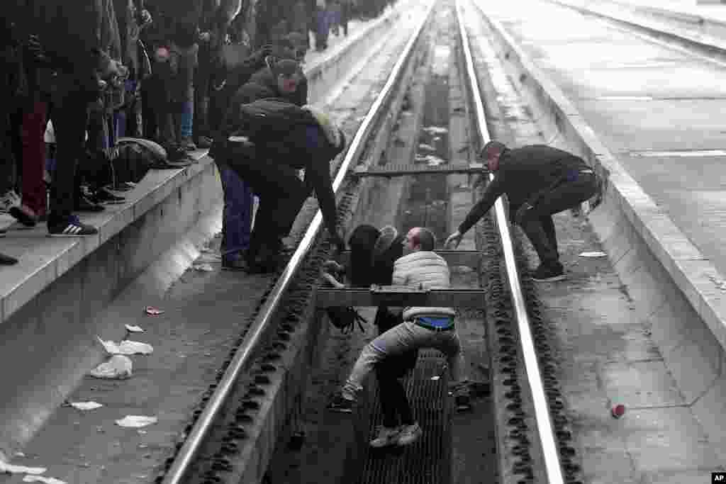 Passengers assist a woman who fell off a platform as she was trying to cross railroad tracks at Gare de Lyon train station, in Paris, as unions stage a mass strike.