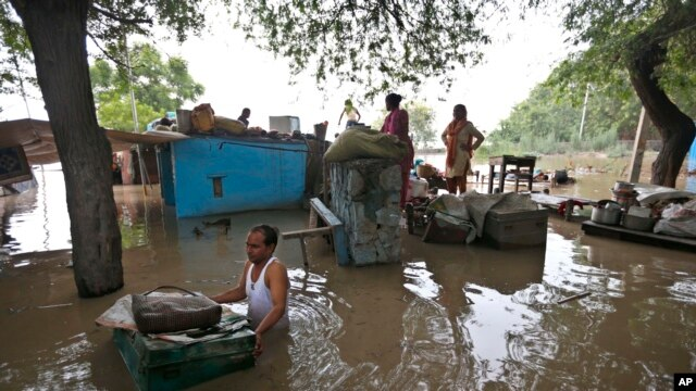 A man drags a trunk to higher ground after floodwaters inundated homes along the banks of the Yamuna River, in New Delhi, India, June 19, 2013.