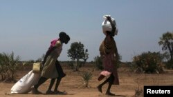 FILE - Women carry food at a food distribution site in Nyal, Unity State. More than one million people have been forced from their homes by the conflict, of which 803,200 have been displaced within South Sudan and 254,600 have fled to neighbouring countr
