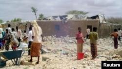 Quelques personnes massées autour des gravats laissés après une frappe aérienne à Dusamareb, Somnalie, 1er mai 2008.