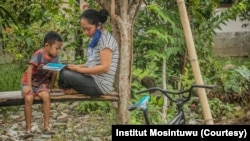 Seorang ibu dan anak yang sedang membaca booklet informasi Virus Corona di Desa Kilo, Kecamatan Poso Pesisir, Kabupaten Poso, Sulawesi Tengah, 30 Maret 2020. (Foto: Institut Mosintuwu)