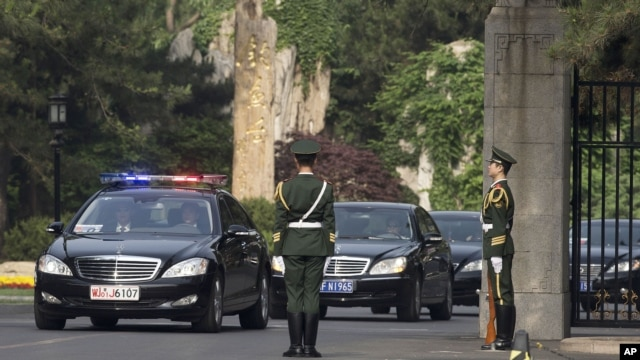 A car, second from left, believed to be carrying North Korean envoy Choe Ryong Hae, is escorted by a convoy of cars as it leaves Beijing's Diaoyutai State Guesthouse, May 24, 2013.