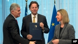 Chairman of the Presidency of Bosnia and Herzegovina Dragan Covic, left, Dutch Foreign Minister Bert Koenders, center, and European Union High Representative Federica Mogherini participate in a handover ceremony of the EU membership Application with Bosnia Herzegovina at the EU Council building in Brussels on Monday, Feb. 15, 2016.