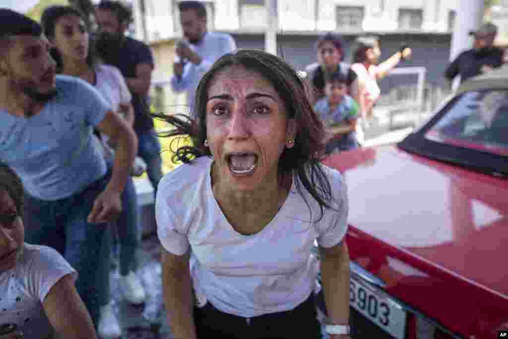 A Syrian woman screams for help for her husband who was injured by stone throwing by members of the Lebanese Forces group, who attacked buses carrying Syrians traveling to vote in the town of Zouk Mosbeh, north of Beirut, Lebanon.