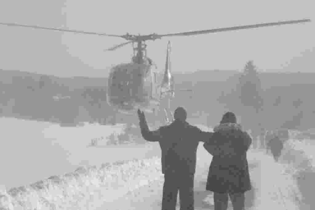 Bosnian people waving to helicopter crew as they wait for food supplies in a remote village, cut off by road due high snow fall, near Bosnian town of Sokolac, 70 kms east of Sarajevo, Bosnia, on February 1, 2012 (AP)