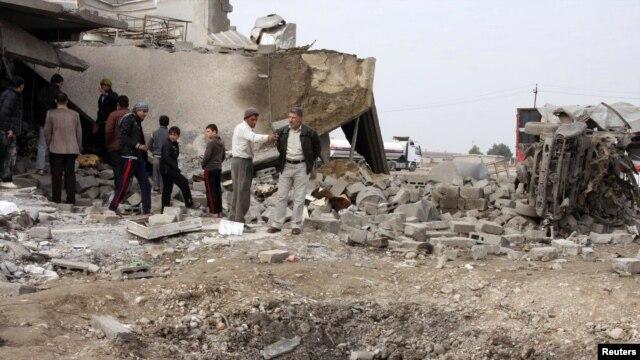 Warga berkumpul di tempat serangan bom di al-Mouafaqiyah, sebuah desa dekat Mosul, 390 kilometer utara Baghdad (17/12/2012). (Reuters/Khalid al-Mousuly)