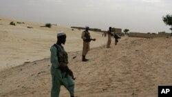 Thành viên nhóm Hồi giáo cực đoan Ansar Dine đứng bảo vệ xung quanh khu vực nơi họ đang chuẩn bị chặt tay của một thanh niên bị kết tội ăn cắp gạo theo luật Sharia ở Timbuktu, Mali.