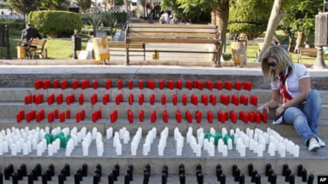 A woman arranges candles with the colors of Syrian national flag during a sit-in for people who were killed during protests in Syria, Damascus, June 29, 2011