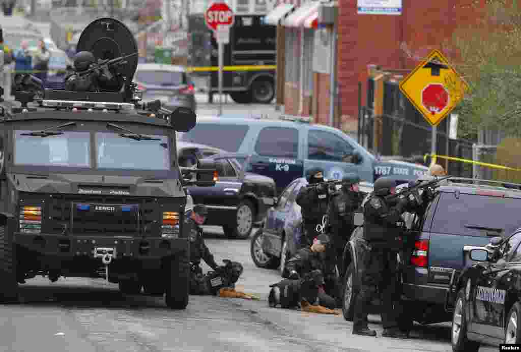 Police officers take position during a search for the Boston Marathon bombing suspects in Watertown, Massachusetts April 19, 2013. Police on Friday killed one suspect in the Boston Marathon bombing during a shootout and mounted a house-to-house search fo