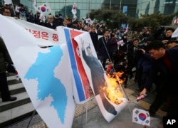 South Korean protesters burn a portrait of North Korean leader Kim Jong Un during a rally against a visit of North Korean Hyon Song Wol, head of North Korea's art troupe, in front of Seoul Railway Station in Seoul, Jan. 22, 2018.