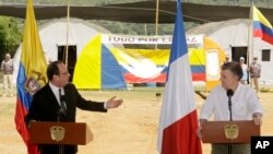 France's President Francois Hollande, left, speaks during a joint statement with Colombia's President Juan Manuel Santos, right, during a visit to a United Nations camp near an area where members of FARC, will turn over weapons to U.N. observers in La Venta, Colombia, Jan. 24, 2017.