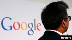 一位男士站在谷歌的标牌前方。(2013年11月4日)