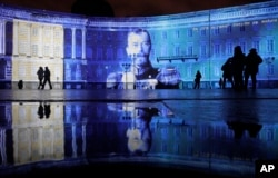 People look at a portrait of the last Russian Czar, Nicholas II, drawn in light at Dvortsovaya (Palace) Square during a light show marking the centenary of the Bolshevik Revolution in St.Petersburg, Nov. 4, 2017.