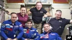 FILE - Expedition 42 crew members aboard the International Space Station in the Zvezda service module.