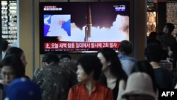 People watch a television news screen showing file footage of North Korea's missile launch, at a railway station in Seoul on August 10, 2019.