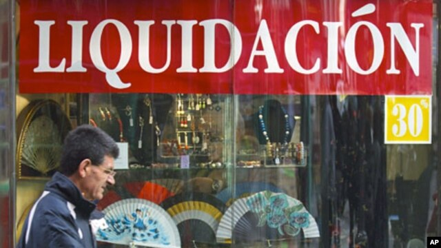 A man walks past a shop selling Spanish fans with a sign reading 'Liquidation' during early sales in Madrid, January 2, 2012