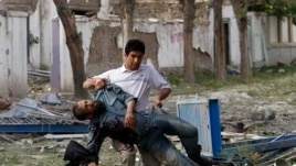 Wounded Afghan policeman is carried away from site of explosion, Kabul, May 24, 2013.