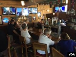 Para pengunjung restoran Harry Buffalo di luar arena debat, menyaksikan acara tersebut melalui televisi (6/8). (VOA/Kane Farabaugh)