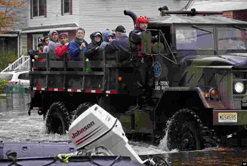 Decenas de personas abordan los camiones de emergencia para huír de las aguas estancadas e inundaciones que dejó el huracán Sandy en Little Ferry, Nueva Jersey.