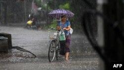 ရန္ကုန္ၿမိဳ႕မွာ မိုးရြာေနခ်ိန္ စက္ဘီးတြန္း သြားေနတဲ့ အမ်ိဳးသမီး တဦး (ဇြန္ ၂၉၊ ၂၀၁၉)