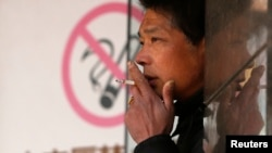 "A man smokes in front of a ""no smoking"" sign outside a shopping mall in Shanghai, Jan. 10, 2014."