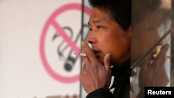 "FILE - A man smokes in front of a ""no smoking"" sign outside a shopping mall in Shanghai, Jan. 10, 2014."
