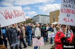 FILE - Demonstrators hold placards during the March for Science Stockholm manifestation at Medborgarplatsen square in Stockholm, Sweden, April 22, 2107.