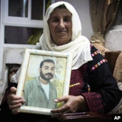 Zahra Falana sits at her home with a picture of her son, Ata Falana, who was relocated to Gaza after being released October 18, 2011.