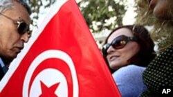 Femme tunisienne tenant un drapeau avec son doigt taché d'encre après le vote dans un bureau de vote à Tunis 23 Octobre , 2011