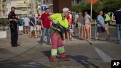 Un agent de la municipalité nettoie le pavement près des policiers déployés sur le lieu de l'attaque à Cambrils, Espagne, 18 août 2017.