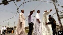 Warga Irak digeledah sebelum memberikan suaranya dalam pemilihan provinsi di Fallujah (20/6). (AP/Khalid Mohammed)