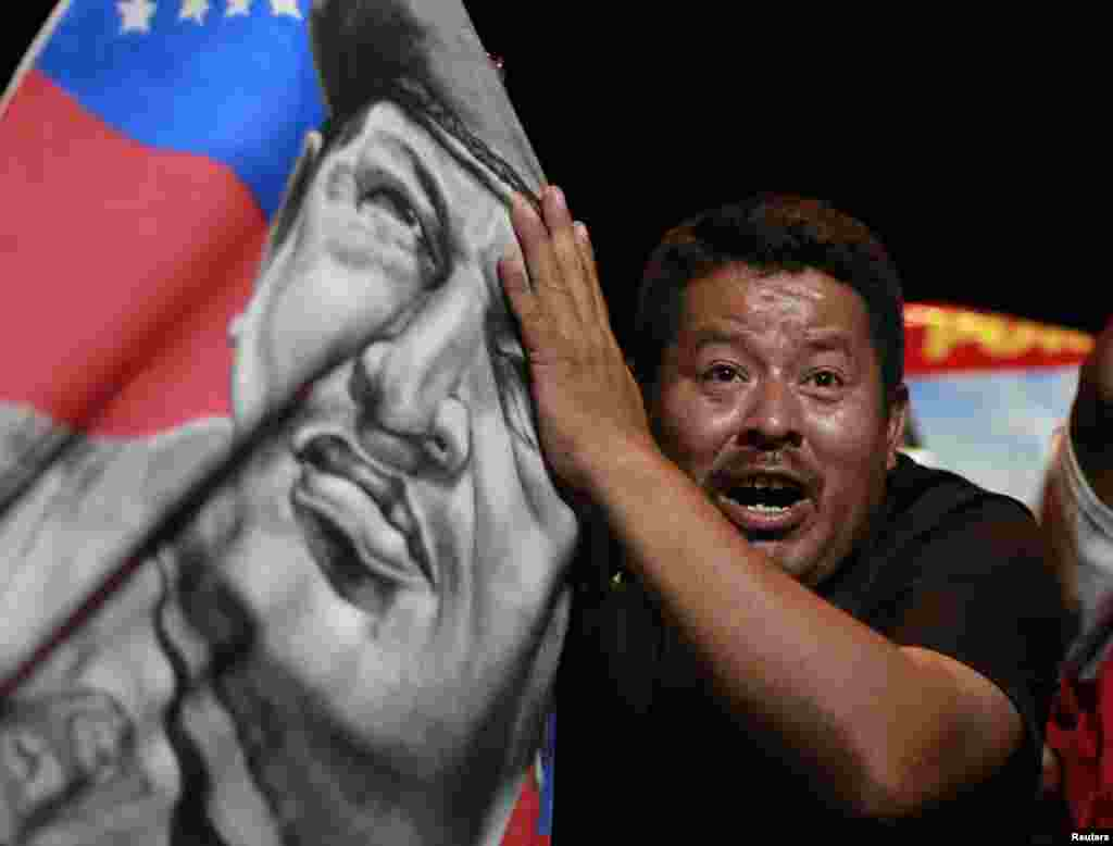 A supporter of Nicolas Maduro holds a banner with an image of late President Hugo Chavez as he celebrates after the official results gave Mr. Maduro a victory in the balloting, in San Salvador, April 14, 2013.