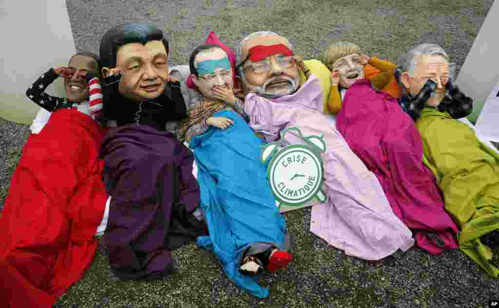 Oxfam activists wear masks of, from left, President Barack Obama, Chinese President Xi Jinping, French President Francois Hollande, India's Prime Minister Narendra Modi, German Chancellor Angela Merkel and Australia's Prime Minister Malcolm Turnbull as they stage a protest during the COP21, United Nations Climate Change Conference in Le Bourget, north of Paris, France.