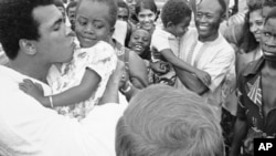 Mohamed Ali plante une bise sur la joue d'une jeune admiratrice zaïroise venue l'applaudir, avec d'autres supporters, à son camp d'entraînement N'Sele au Zaïre, 26 octobre 1974. (AP Photo)