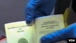 Seorang Polisi Spanyol menunjukkan sebuah paspor palsu hasil penggerebekan di Barcelona.