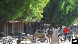 Mutane sun tsere suna tsallake shingaye, kuma sun rufe shagunansu biyo bayan harin kunar bakin waken na, Maiduguri, Najeriya, Talata, Nuwamba 25, 2014.