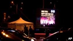 Polisi-polisi India berjaga di dkap papan bertuliskan pesan Selamat Tahun Baru di Hyderabad, India, 31 Desember 2016 (Foto: dok).