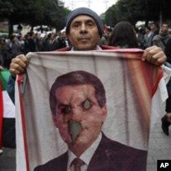 Un manifestant tunisien et le visage effacé de l'ancien dirigeant de la Tunisie