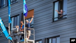 Pitrik van der Lubbe waves from a crane to his 88-year-old father Henk, right, at a nursing home in Gouda, Netherlands. (AP Photo/Peter Dejong)